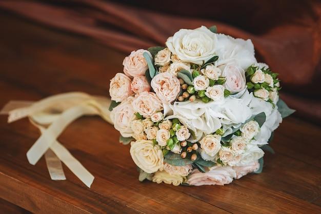 木製の表面にバラのウェディングブーケ。結婚の概念