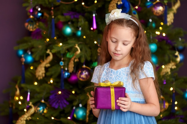 クリスマスツリーの近くのギフトボックスを持つ少女