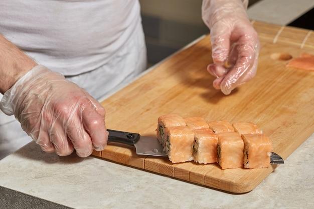 Шеф-повар готовит суши. готовим рулетики с лососем