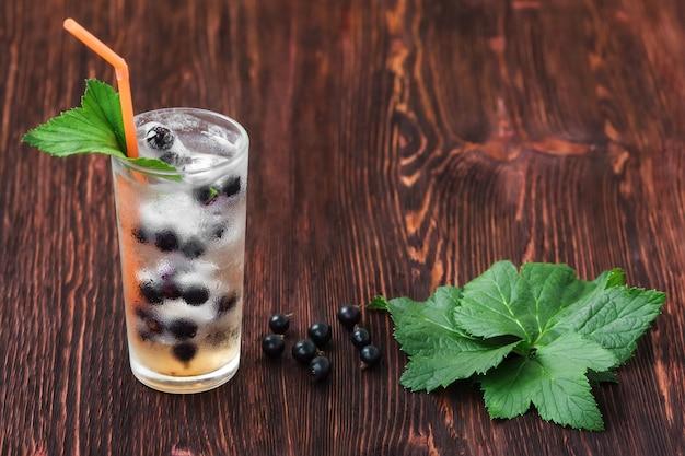Стакан свежей смородины со льдом, коктейль на деревянный стол