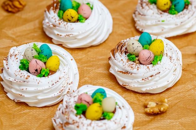 卵、イースターのお菓子とミニパブロワメレンゲの巣