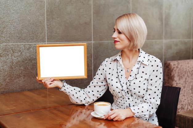 Женщина в кафе держит деревянный каркас, пустой белый макет