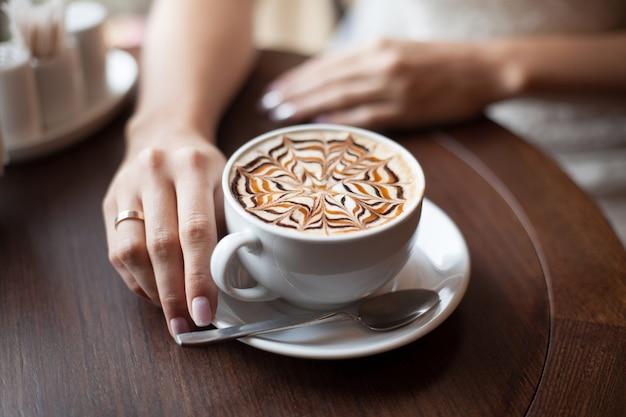 ラテアートコーヒーカップと花嫁の手。セレクティブフォーカス