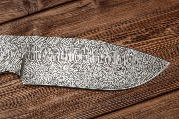 木製の表面に手作りの狩猟ダマスカス鋼ナイフ