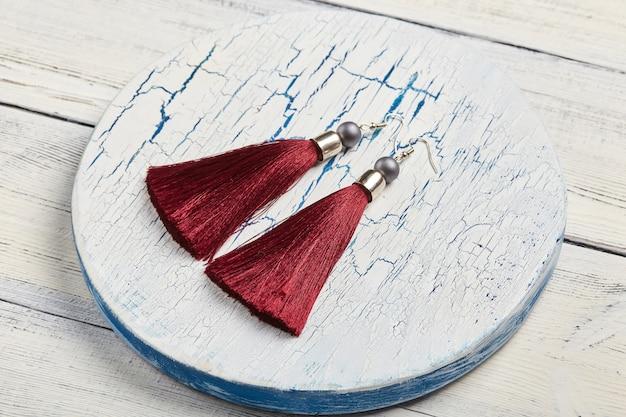 Серьги с красными кисточками на белой поверхности