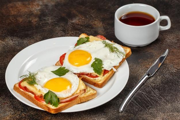 Бутерброд с сыром, беконом, помидорами и жареным яйцом на тарелке