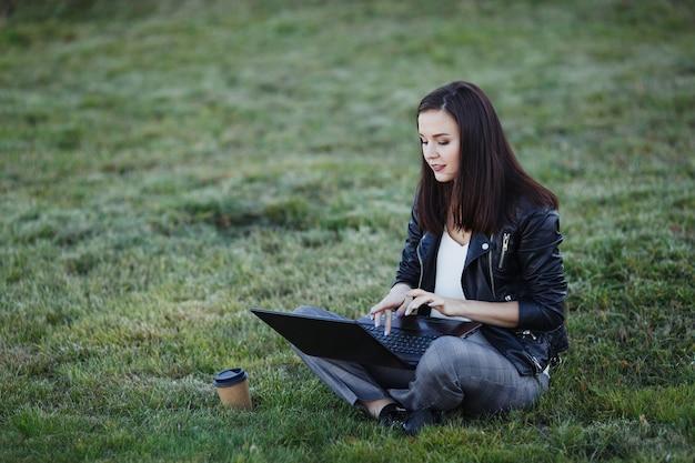 座っているとラップトップで公園で働く若いビジネス女性