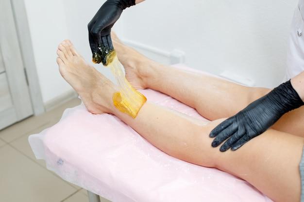 Косметолог, применяя подслащивающую депиляцию на ноге
