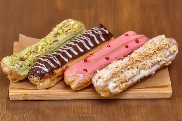 Красочные эклер торты с кремом на деревянной доске