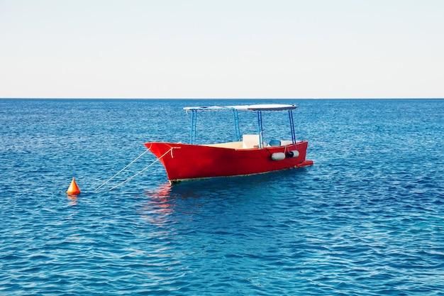 ターコイズブルーの海で空の漁船