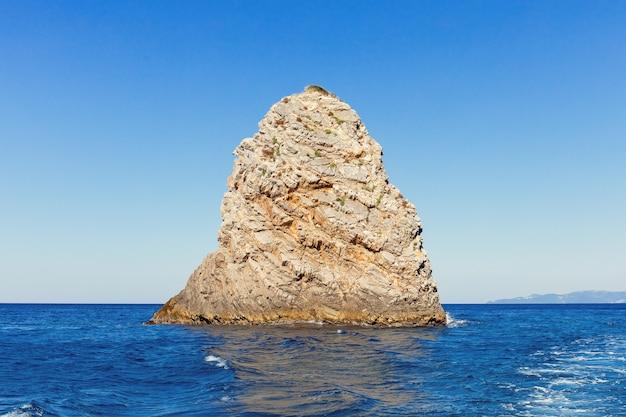 Одиночный камень с чистой голубой морской водой