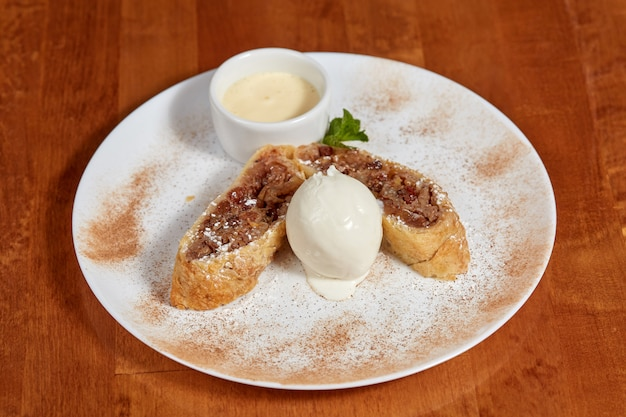 Яблочный штрудель с шариком мороженого на тарелке