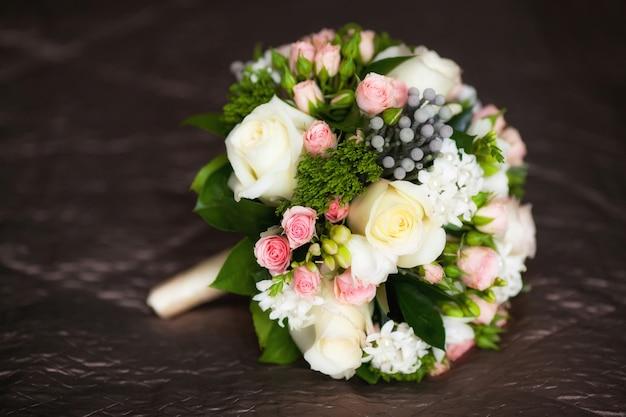 Крупным планом красивый свадебный букет на темном столе