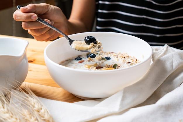 健康的な朝食。木製のテーブル背景に新鮮なグラノーラ、牛乳とベリーとミューズリーを食べる若いアジア女性。