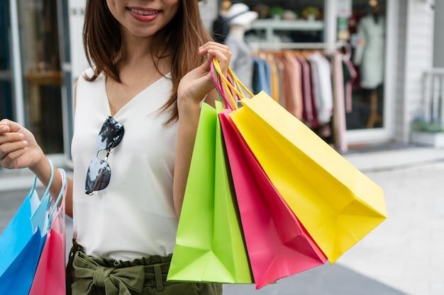 ショッピングやバッグ、クローズアップ画像を保持している幸せな女性の概念。
