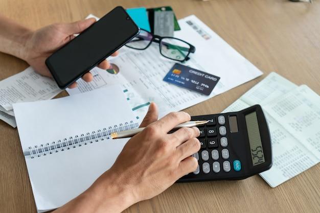 Человек держа мобильный телефон и используя калькулятор, учет и концепцию сбережений