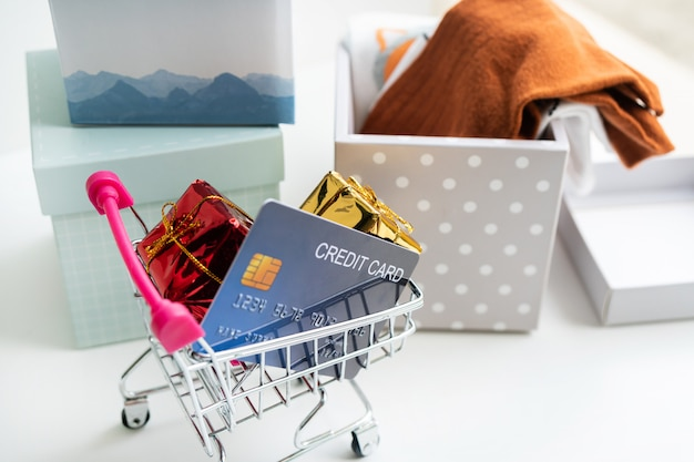 オンラインショッピングの概念。ショッピングカート、宅配ボックス、クレジットカード、自宅の机の上。コピースペース、クローズアップ