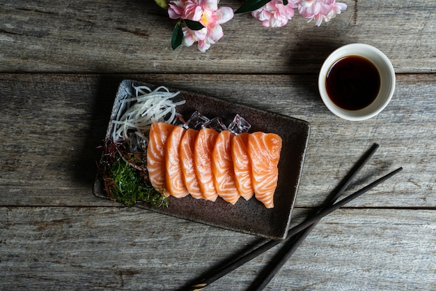 木製のテーブルに醤油とサーモン刺身和食