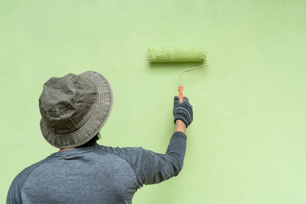 Задний взгляд художника молодых человеков в футболке и перчатках крася стену с роликом краски.