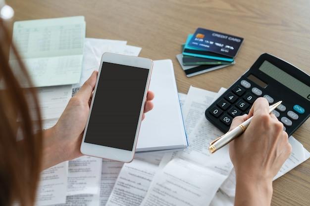 Женщина держа мобильный телефон и используя калькулятор, учет и концепцию сбережений.