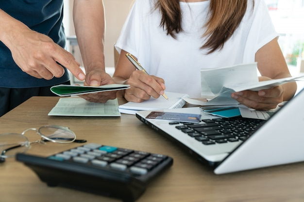 Семейный бюджет и финансы. молодая женщина делает счета вместе с мужем дома,