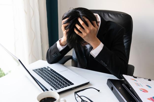 Деловой человек держит голову проблемы с долгами в офисе