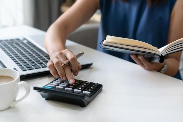 ホームオフィスでノートに財務書類を見ながら電卓を使用して美しい若い笑顔アジア女性実業家。