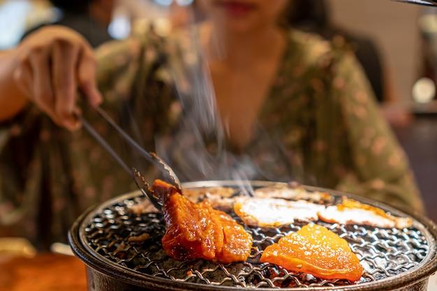 女性は生の豚肉を炭ストーブ、韓国のバーベキューまたは焼肉スタイルで焼きました。