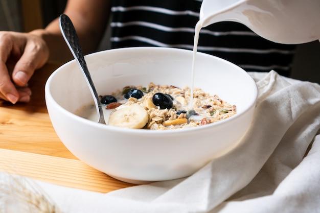 健康的な朝食。新鮮なグラノーラ、ミューズリー、ミルク、ブルーベリー、木製の背景にバナナ。