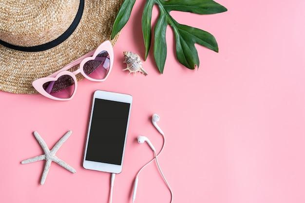 ピンクの背景にフラットレイアウト旅行者アクセサリー。トップビュー旅行や休暇の概念。夏の背景。