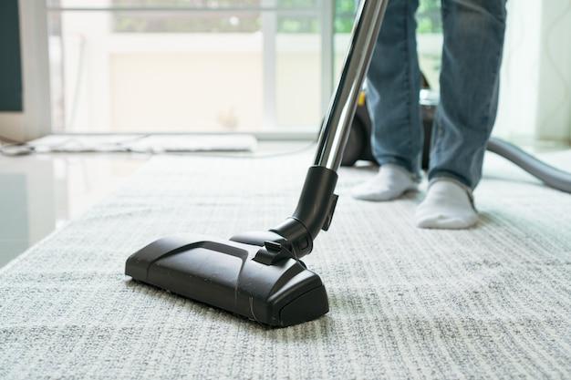 リビングルームで掃除機のクリーニングカーペットを使用している女性。