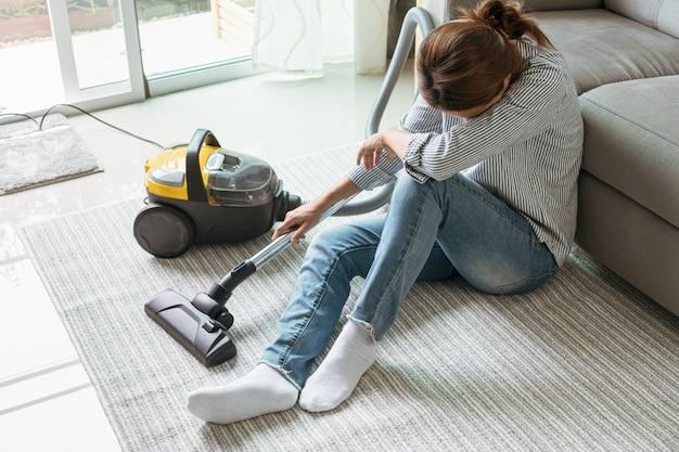 リビングルームで掃除機掃除カーペットを使用した後、床に座っている女性。