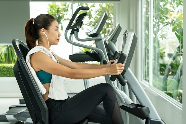朝のスリムでしっかりした健康のためにマシンエアロビクスで減量する女性のフィットネスジムでエクササイズバイク有酸素運動。