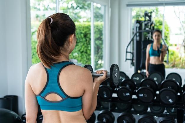 Женщина делает упражнения с гантелями в тренажерном зале.