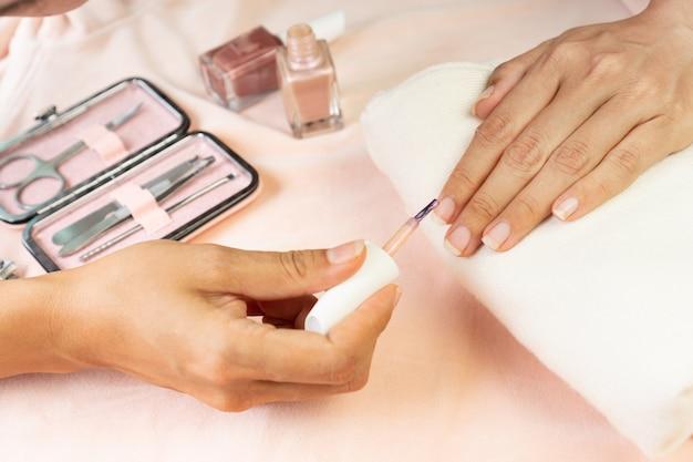 マニキュア器具とピンクシルクベルベットのツールのセットでパールピンク色のマニキュアをしている女性の手。美しさ、マニキュアのコンセプト