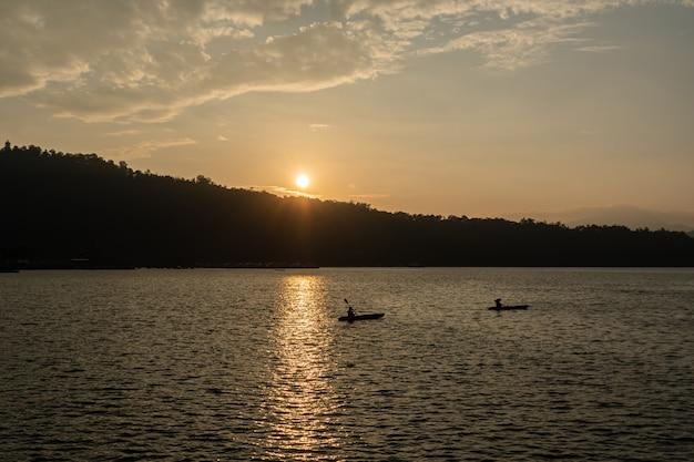 Путешественник каноэ на озере во время заката.