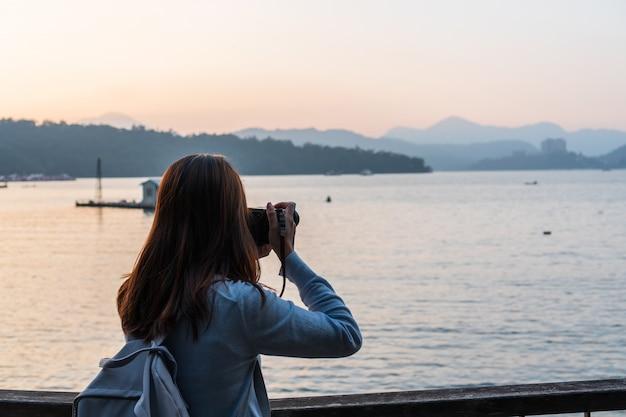 若い女性は彼女の前の景色で写真を撮る。