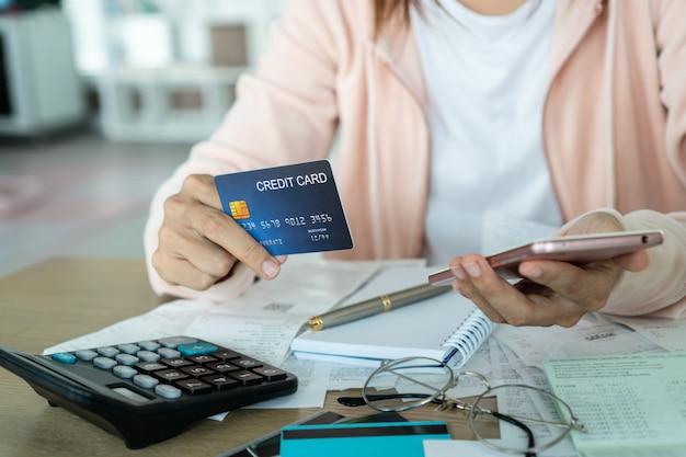 Женщина держа кредитную карточку и и концепция сбережений.