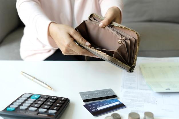 彼女の机で毎月の費用を計算するために彼女の財布をチェックする若いアジアの女性。家の節約のコンセプト。金融と分割払いのコンセプト。閉じる。