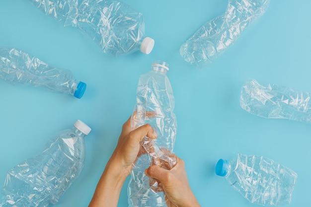 Разбитые пластиковые бутылки на синем
