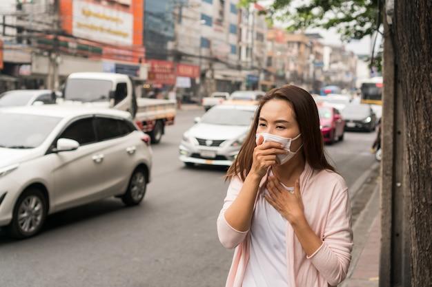 Портрет молодой азиатской девушки нося маску в улице города.