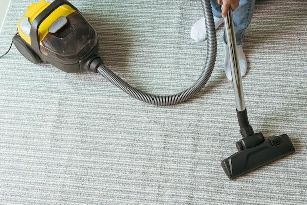 リビングでカーペットを掃除する掃除機を使う女性。