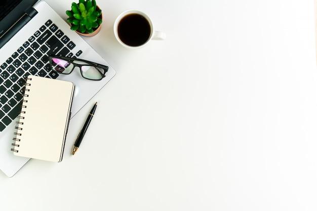 コーヒーカップとノートパソコン、ノートブック、その他の作業用品と白いデスクオフィス。トップビュー、コピースペース、フラットレイアウト。
