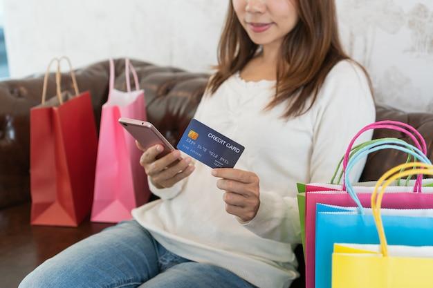 アジアの女性がクレジットカードと自宅のソファーに座っている携帯電話、技術、デジタルライフスタイルのデジタルライフスタイルとオンラインショッピング