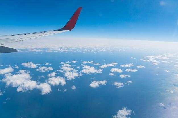 飛行機の窓、空の景色、曇りからの眺め。飛行と旅行のコンセプトです。