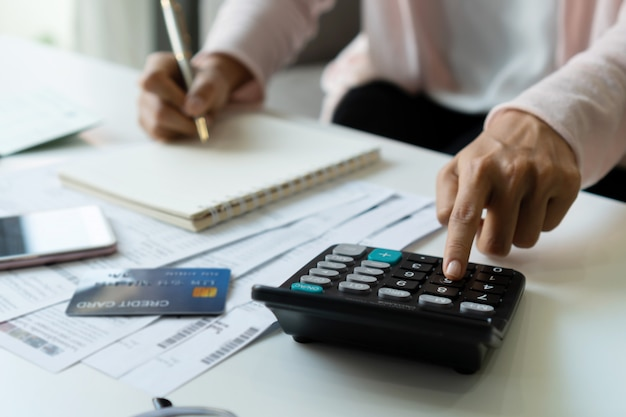 Молодая азиатская женщина расчетливые ежемесячные расходы на ее столе. концепция сохранения дома. финансовая и рассрочка платежа концепции. закройте