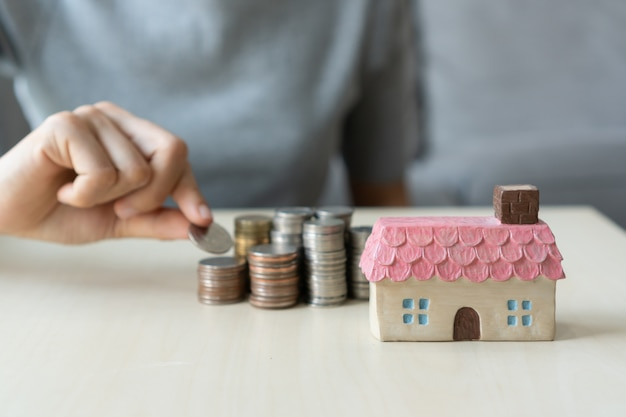 コイン、お金のスタック、おもちゃの家をテーブルに持っている手を閉じて、将来のために保存し、成功、財務の概念を管理します。