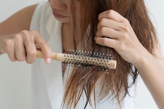 お風呂の後に彼女のぬれた厄介な髪を櫛、薄毛の問題でブラッシングする女性。髪のダメージ、健康と美容のコンセプト。