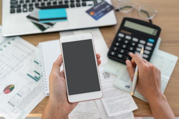 Женщина держа мобильный телефон и используя калькулятор, учет и концепцию сбережений