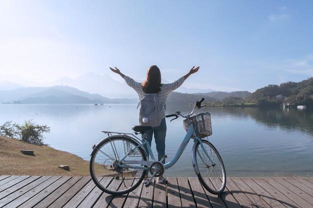 Молодая красивая девушка стоит возле велосипеда, а остальные руки вверх на велосипеде след на озере в первой половине дня. активные люди. на открытом воздухе
